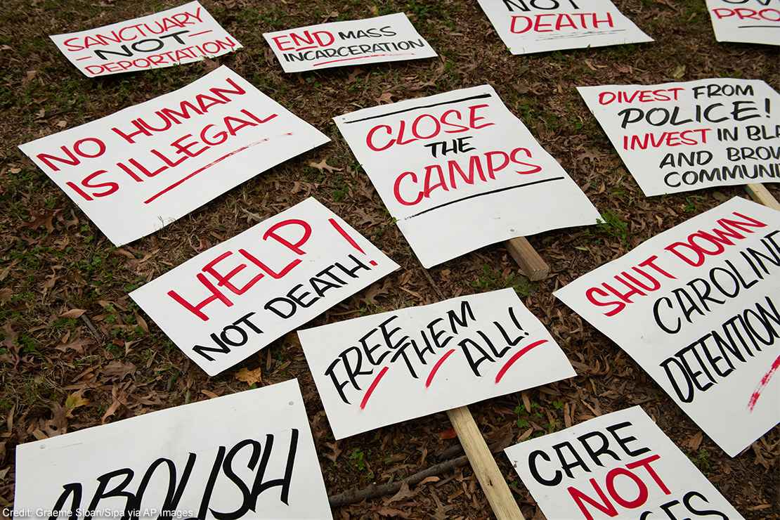 Several signs with calls to end mass incarceration and advocate for the rights of immigrants lying in the grass.